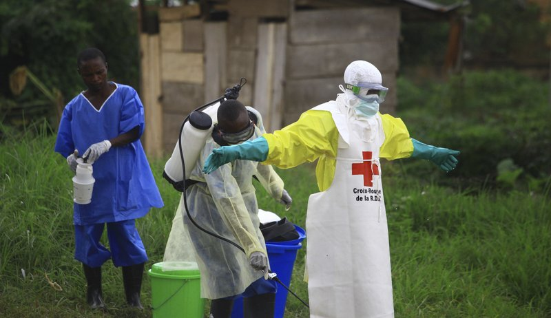 Health official being disinfected after working in one of the many aid centers.  Photo:  Al-Hadji Kudra Maliro/AP
