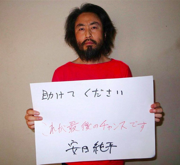 "Japanese freelance journalist Jumpei Yasuda in May 2016, holding a handwritten sign in Japanese that reads: ""Please help. This is the last chance."" NBC News."