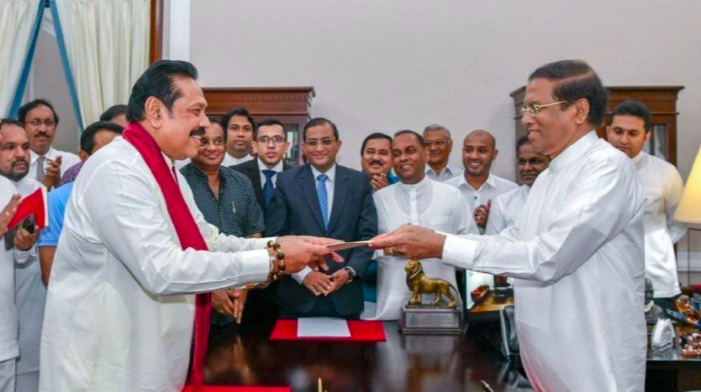 President Sirisena (right) handing materials to former president Rajapaksa (left) on October 26, 2018; Photo:  Los Angeles Times