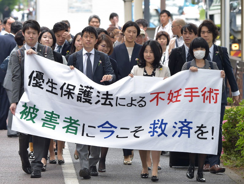 Supporters and lawyers for a Tokyo man who filed suit against the government seeking compensation for being subject to forced eugenic sterilization surgery rally outside of the Tokyo District Court on May 17, 2018. Credit:  Mainichi Shimbun