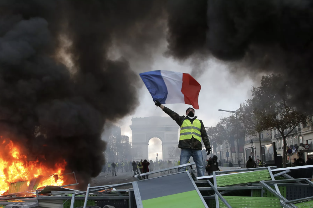 Protestors wearing yellow vests wave the French flag along the Champs Elysées. Source:  Michel Euler/AP