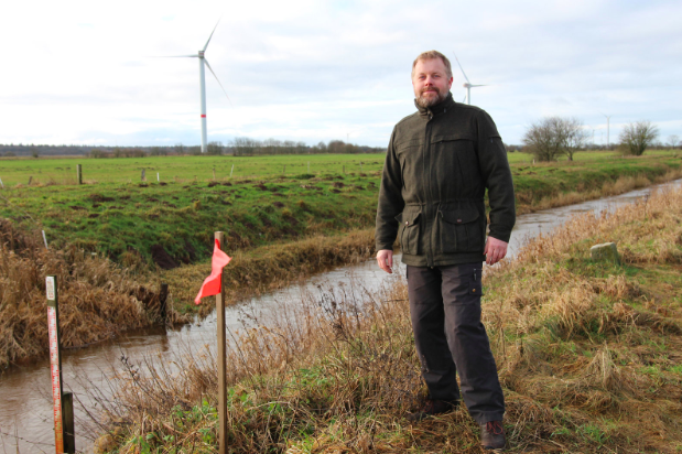 Hans Kristensen, a Danish hunter and forest engineer, stands alongside a flag marking the path of Denmark's planned border fence. Photo:  Sidsel Overgaard/NPR