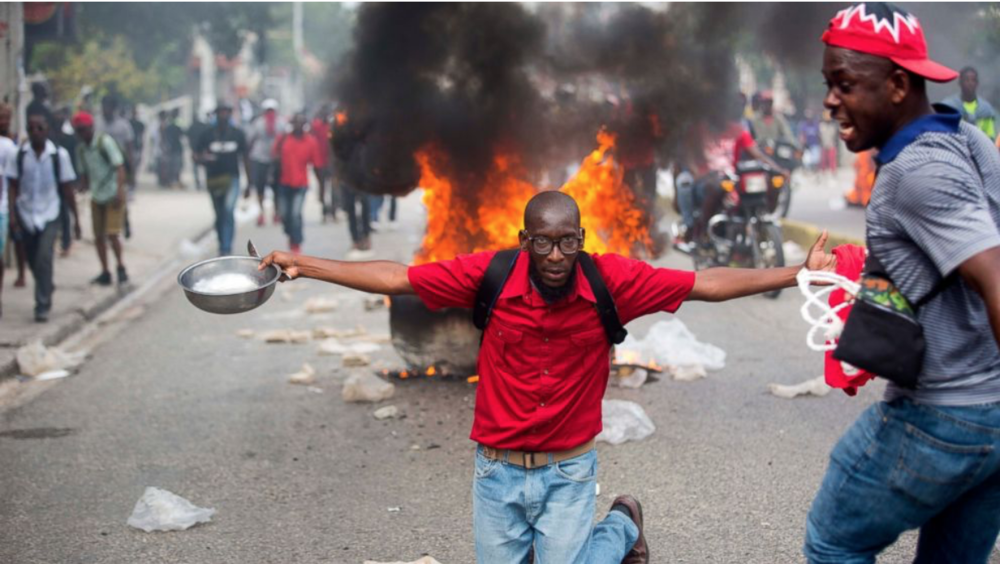 A demonstrator with a bowl and spoon to protest hunger in Haiti.  Source: The Associated Press/ ABC News