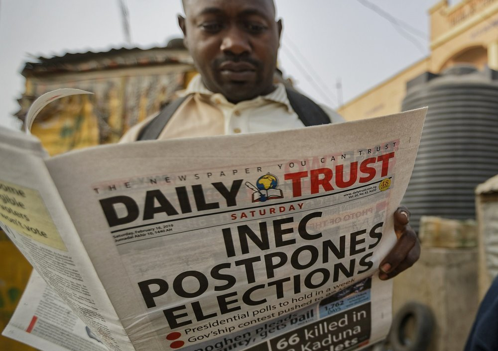 Man reads Newspaper the morning of the postponement of elections is announced. Photo:  AP Photo/ Ben Curtis .