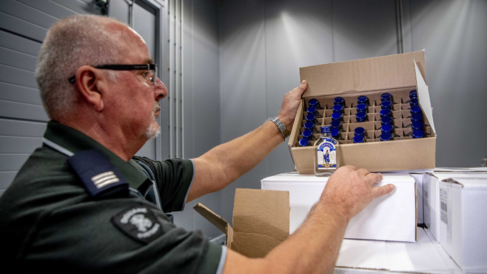 """A Dutch customs official displays bottles of """"Stolbovaya"""" vodka seized by Dutch authorities at the port of Rotterdam allegedly headed for North Korea. Photo:  Robin Utrecht/EPA/TASS"""