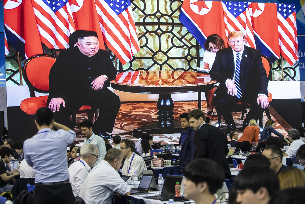 Media members and affiliates work below a screen showing video of North Korean Supreme Leader Kim Jong-un and US President Donald Trump at their high-profile summit in Hanoi, Vietnam on Feb. 28, 2019. Photo:  Justin Chin/Bloomberg