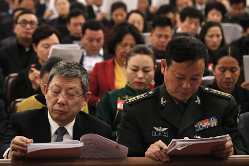 Delegates read work reports delivered by Chinese Premier Li Keqiang during the opening session of the National People's Congress in the Great Hall of the People on Mar. 5, 2019. Photo:  Andy Wong/AP