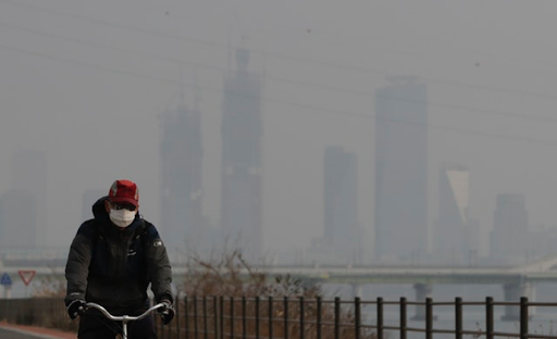 A biker commuting to work wears a face mask to protect himself from the unhealthy air. Photo:  Lee Jin-man/AP