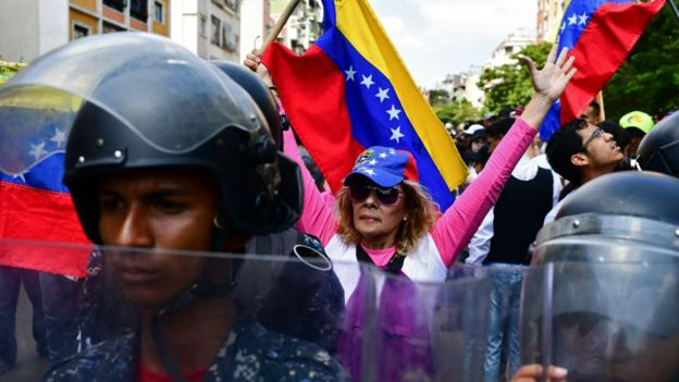 An opposition protester in Caracas on Saturday. Photo: AFP via  BBC News .
