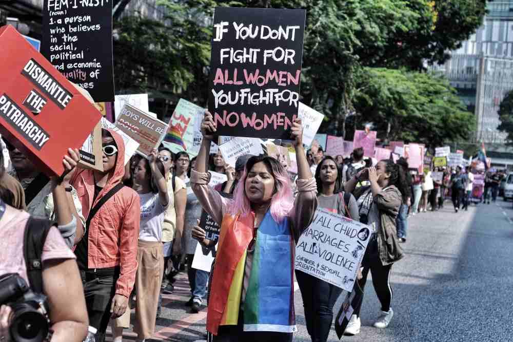 Demonstrators carry posters supporting women's rights in Kuala Lumpur. Photo:  Shafwan Zaidon .