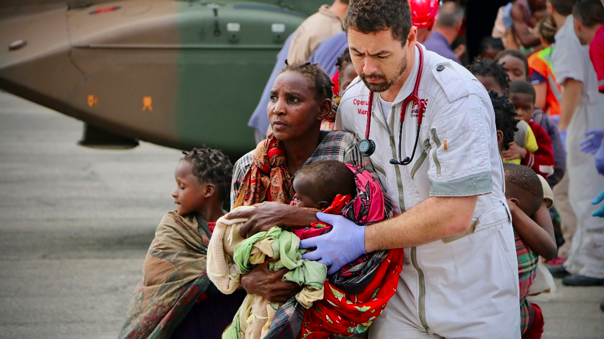 Aid workers are escorting people to safety at the airport of the city of Beira in central Mozambique. Photo:Adrien Barbier/ AFP via Al Jazeera .