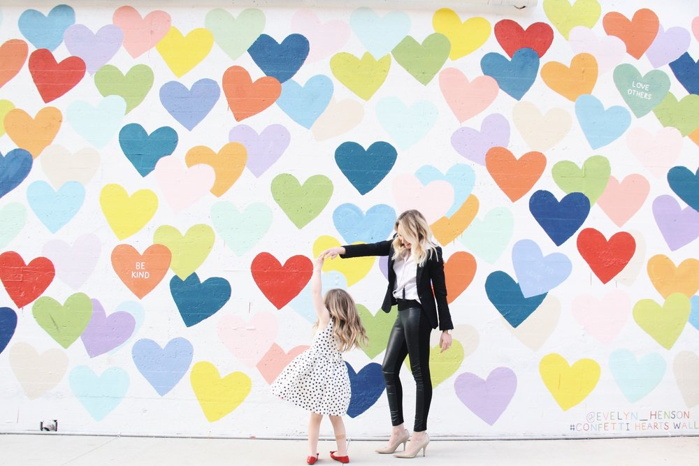 Emily and her daughter twirling at the confetti hearts wall in Charlotte.