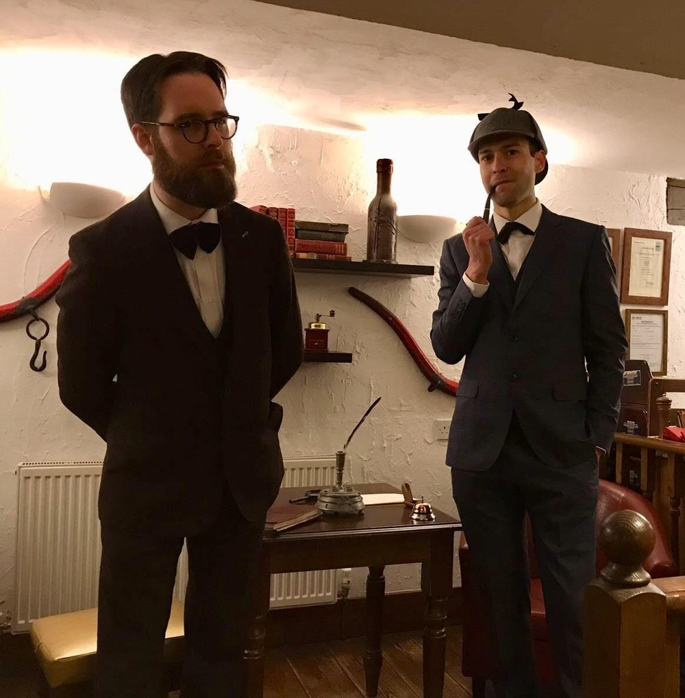 Holmes looks on, amused, as Watson regards the audience suspiciously.