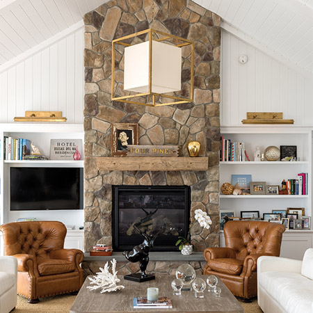 Hurlbutt Designs Cape Porpoise Cottage renovation photo featuring a beautiful stone fireplace, built-in's and gorgeous gold accents.