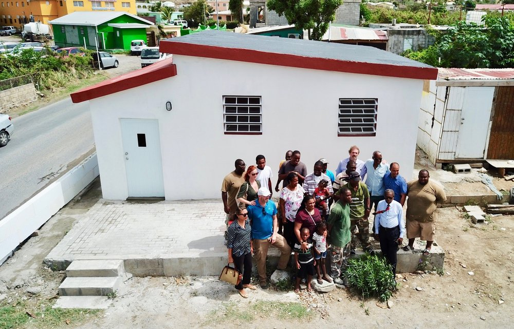July 20, 2018, Sucker Garden road, Sint Maarten   The Romney family (center with children) receive their new home, with Jason Brisebois of SXM Project, Henri Brookson of Foundation Community Aid Sentry Hill, Acting Governor Reynold Amando Groeneveldt and the construction team.