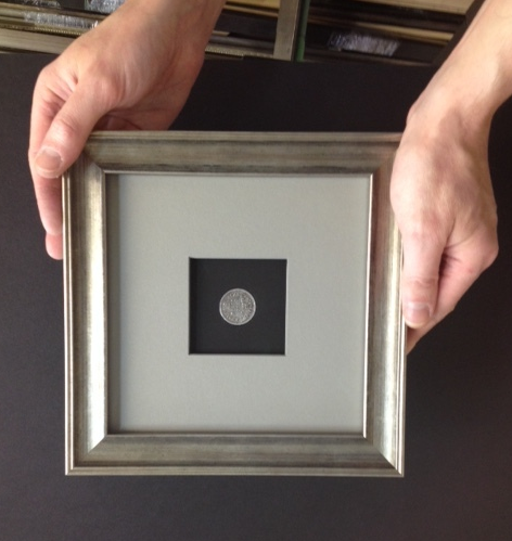 Collectible Coin in Raised Mat and Silver Leaf Frame - This special coin was custom-mounted in a black mat with a tiny circle cut in the center. The grey mat surround adds volume to the design and it is raised to create a dramatic window. The back of the coin can also be viewed through plexiglas on the back.