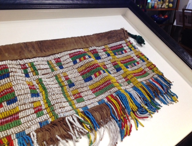 Beaded Skirt from Africa in a Shadowbox - A heavily beaded skirt with leather trim required special treatment for presentation. Our framer sewed it onto a linen mat and added matching shadowbox strips for depth. A leather-wrapped frame finished the rich and elegant design.