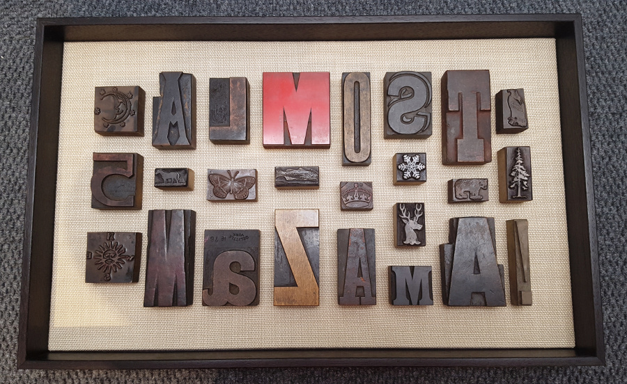 Vintage Lead Type Collection Mounted On Linen For Display - A client's collection of vintage lead type from European flea markets made a great display on a rough-weave linen backboard. Each block was mounted securely and a narrow walnut frame completes the design.
