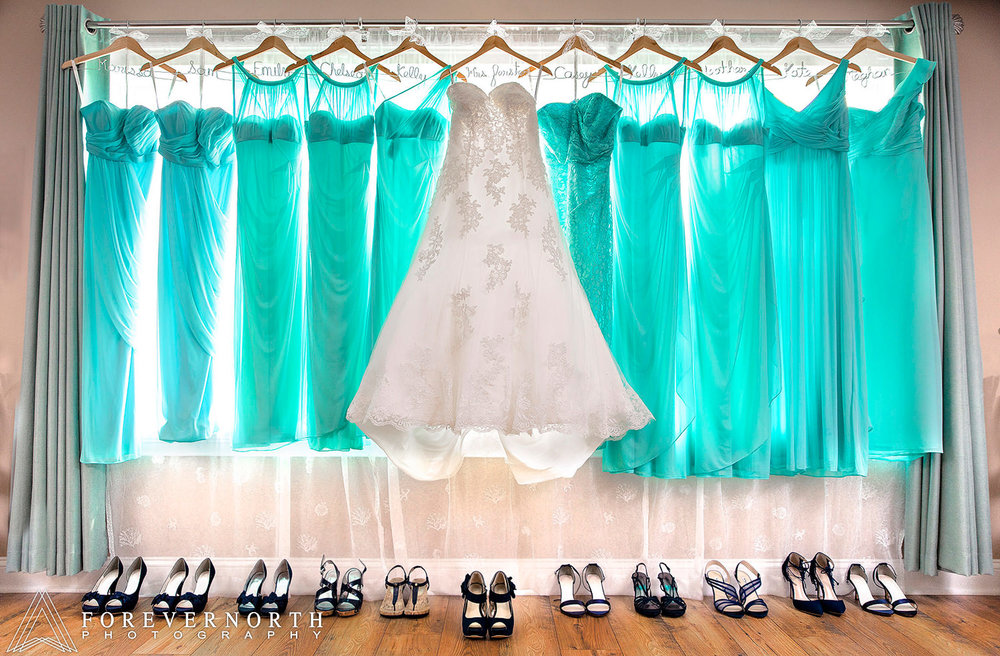 The bride's dress and bridesmaids dresses hanging with the shoes on the ground.
