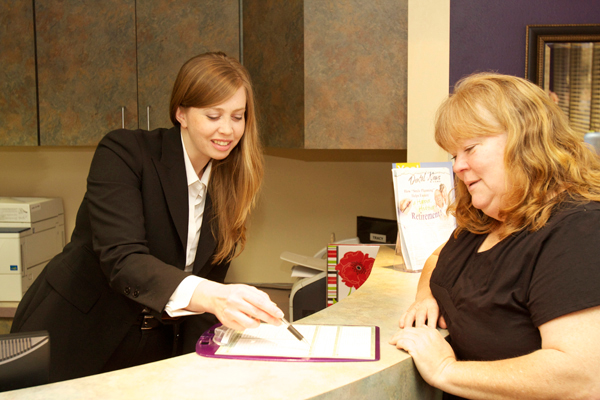 Front desk staff instructing patient on their payment options
