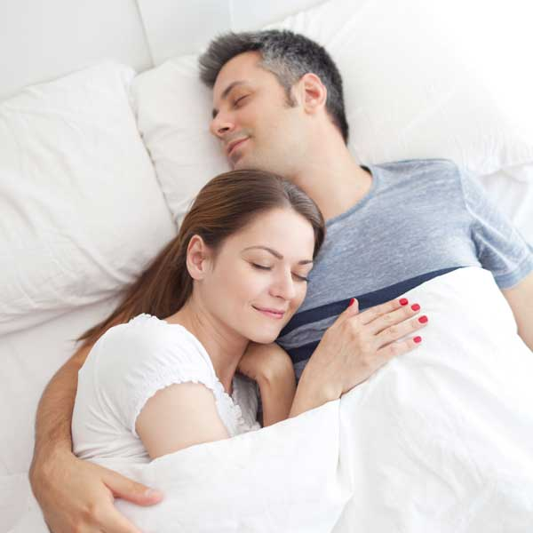 Husband and wife cuddled in bed with no snoring
