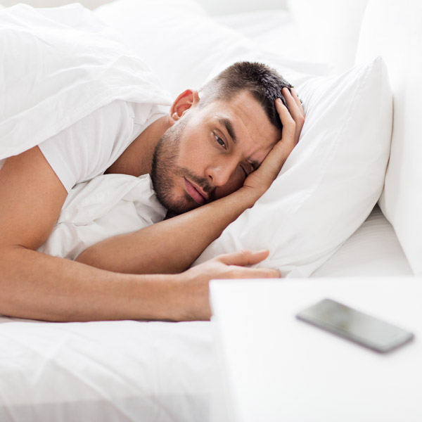 Man laying in bed staring sleepy-eyed at his phone.