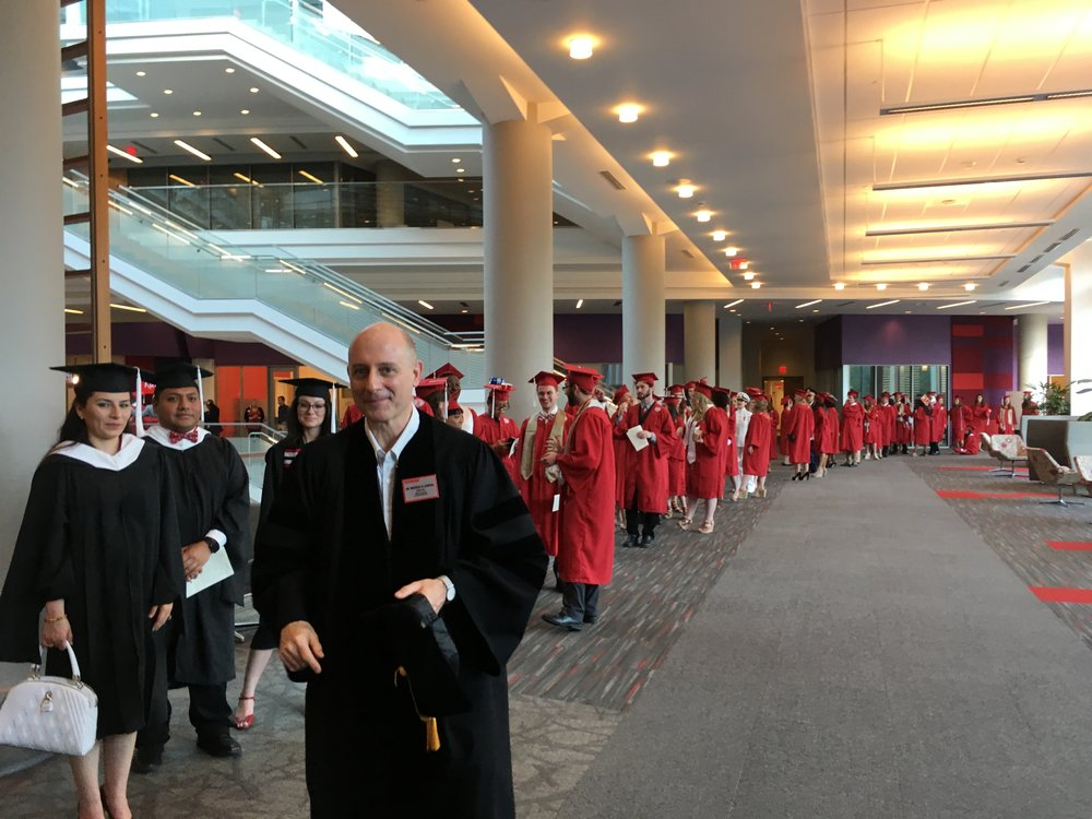 Dr. Michael Garval, Director of Masters of Arts in Liberal Studies, and graduating students about to process