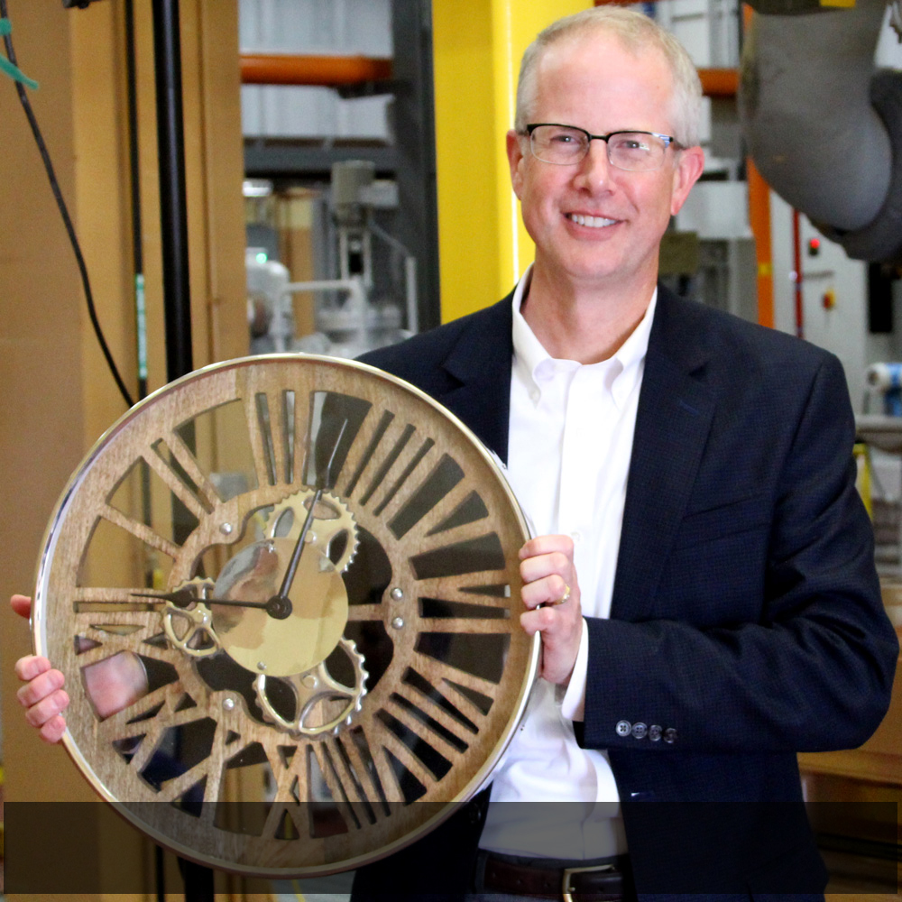 SMMPA Executive Director and Chief Executive Officer Dave Geschwind poses with a clock that was bestowed as a gift to the Owatonna Energy Station.