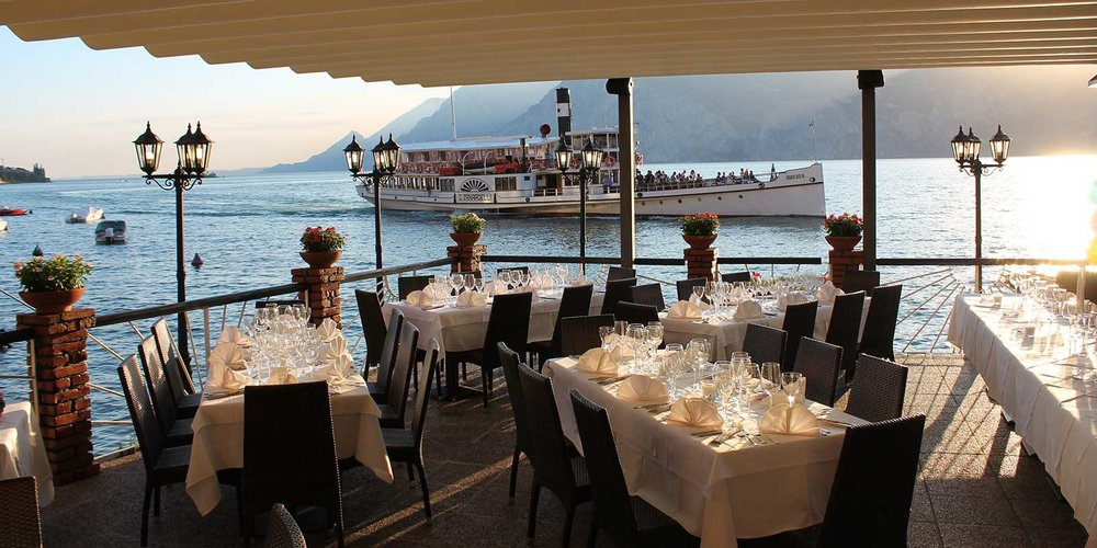 Treccani   Proprio nel centro città, con vista sul lago di Garda meridionale e Campione del Garda. Il ristorante è aperto 24 ore su 24 e offre un menu molto ampio con deliziose specialità locali. Consigliamo di prenotare. Piazza Turazza Don Quirico, 8, 37018 Malcesine VR, Italia +39 045 657 0431 www.ristorantetreccani.it