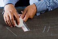 2. Drafting a Pattern:  After the cutter has drafted the individual's pattern, it is then cut out and chalked onto the cloth.
