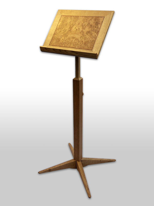 'Jensen' lectern - Commissioned by a retired English language Professor, this oak lectern was intended to help him continue reading, despite his severe arthritis, which prevented him from sitting for long periods at a time.  The height adjustment therefore enables him to position his book comfortably and securely both when sitting and standing.  A custom made spring mechanism and easy to hold handle, to set the height, should mean that this piece will continue to be useable for many years to come, even if his condition worsens.Dimensions: Height 100/150cm, width 50cm, depth 50cm Price: £1450