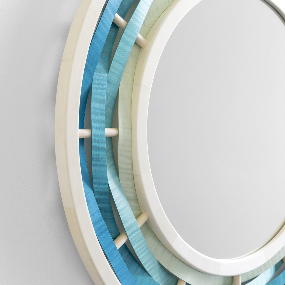 'Watul' mirror - I wrestled with the intricacies of this design off and on for many months but it was worth the effort! Inspired by my home on the Isle of Wight the original design, in blue, draws on water, waves, ships wheels and portholes whilst ripple sycamore veneers further strengthen its nautical feel.I see this mirror as the perfect addition to a minimalist beach or boat house, but perhaps a version in green could be placed to mirror rolling hills, or maybe one with deep reds in a comfy snug? My coloured veneers are pressure dyed by fellow craftsman Kevin Stamper and can be produced in almost any colours and shades.Dimensions: Depth 35cm, diameter 75cmPrice: £1,900
