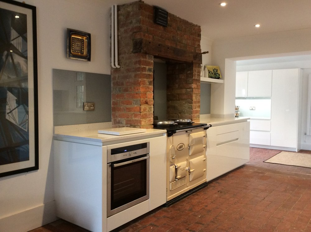 Traditional kitchen with white theme and red brick floor and red brick chimney breast.
