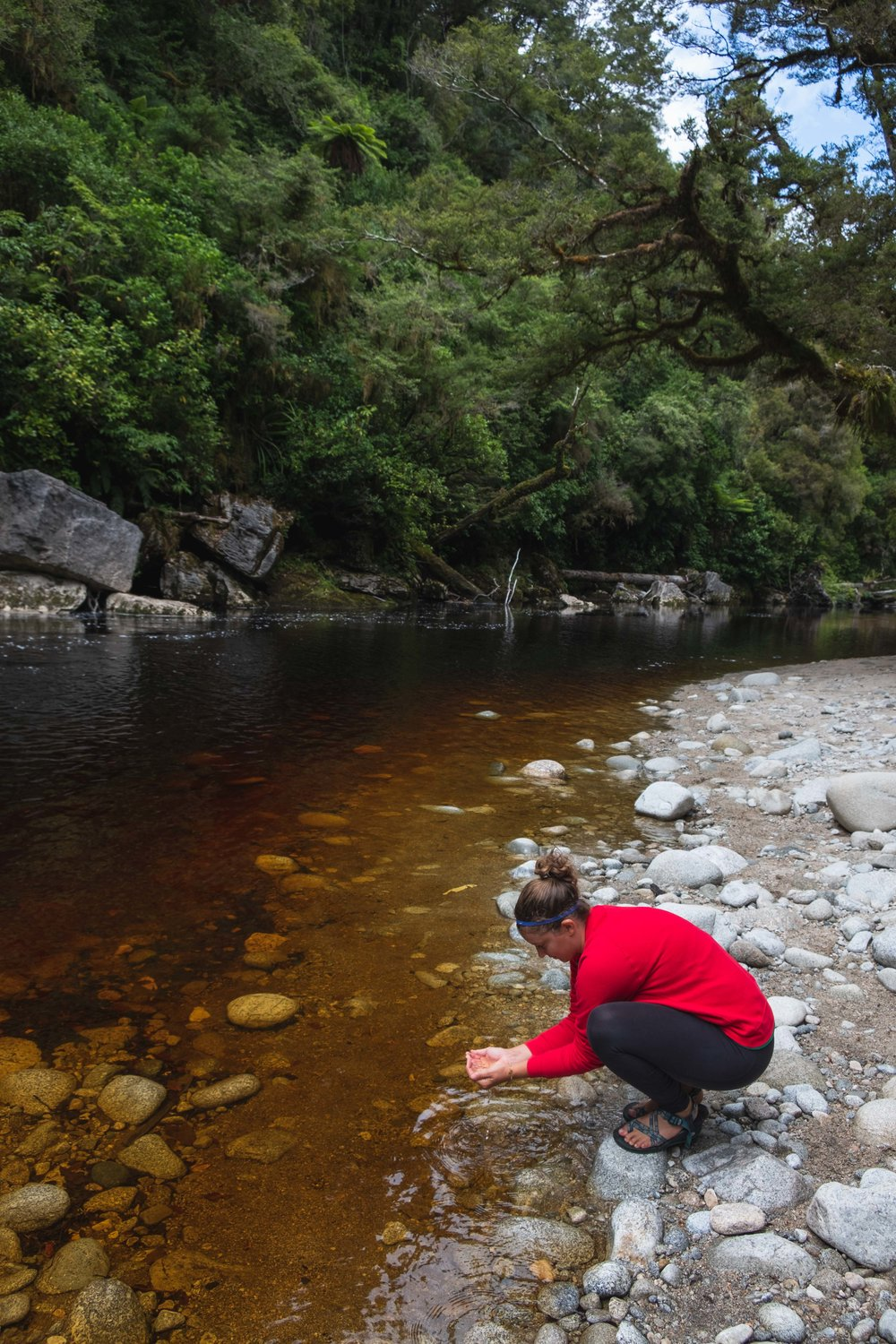 Touching the clear, brown water. Weirdly cool.