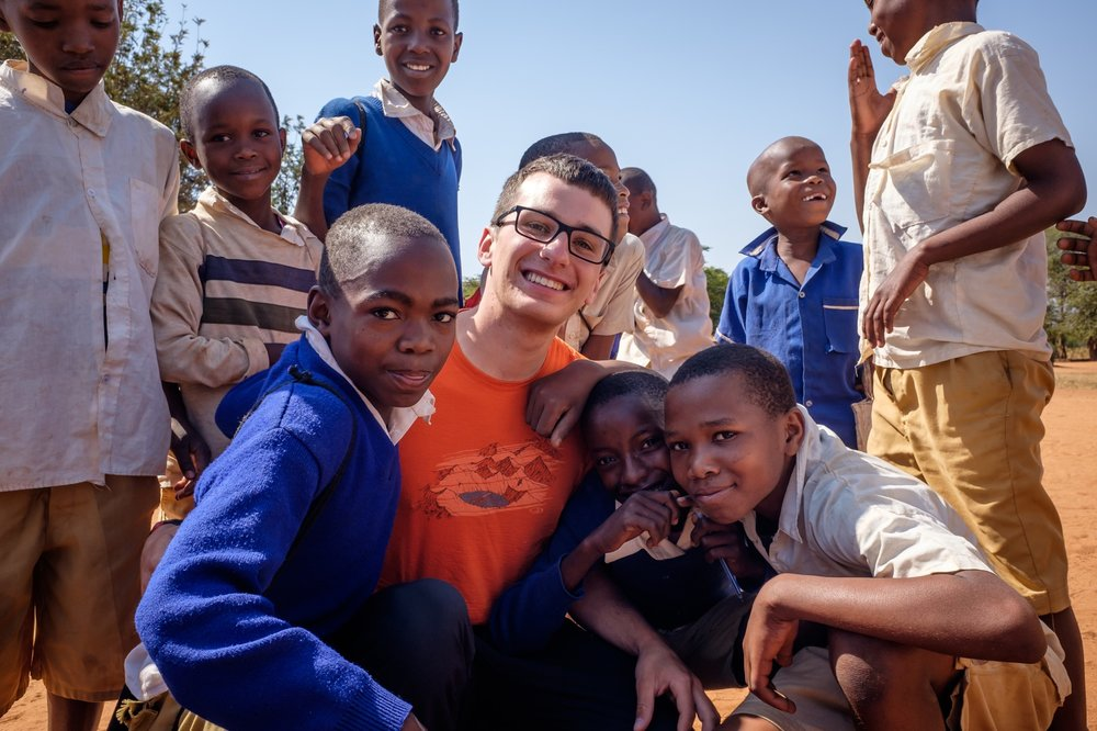 During one of our village visits, students from a local primary school snapped this photo of me with some new friends while playing with my camera.
