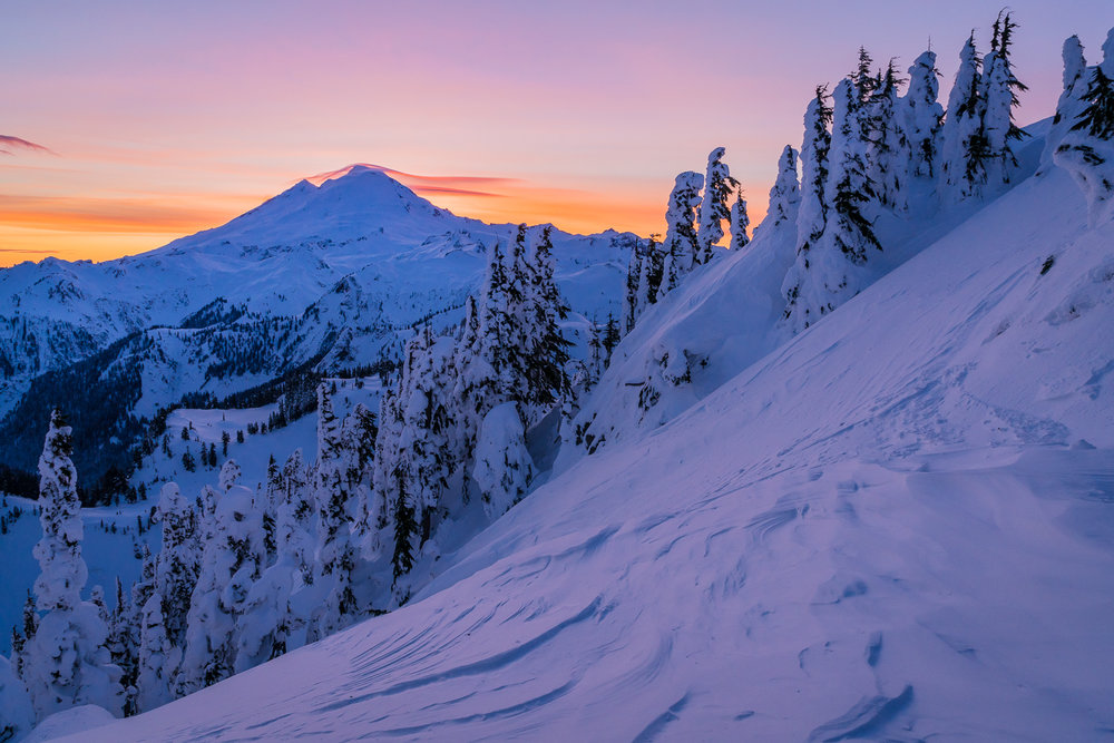 Lenticular clouds settling on the summit of Mount Baker are backlit at sunset, as seen from Shuksan Arm.
