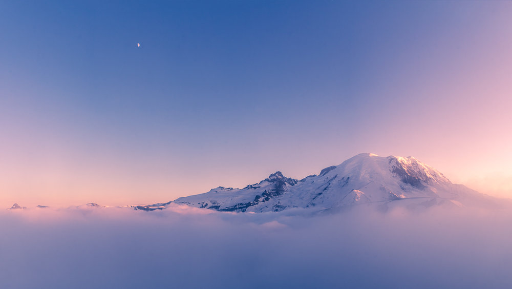 From the very crest of Sourdough Ridge I popped just high enough above the undercast to glimpse the last rays of sun on the northwest slopes of Mount Rainier.