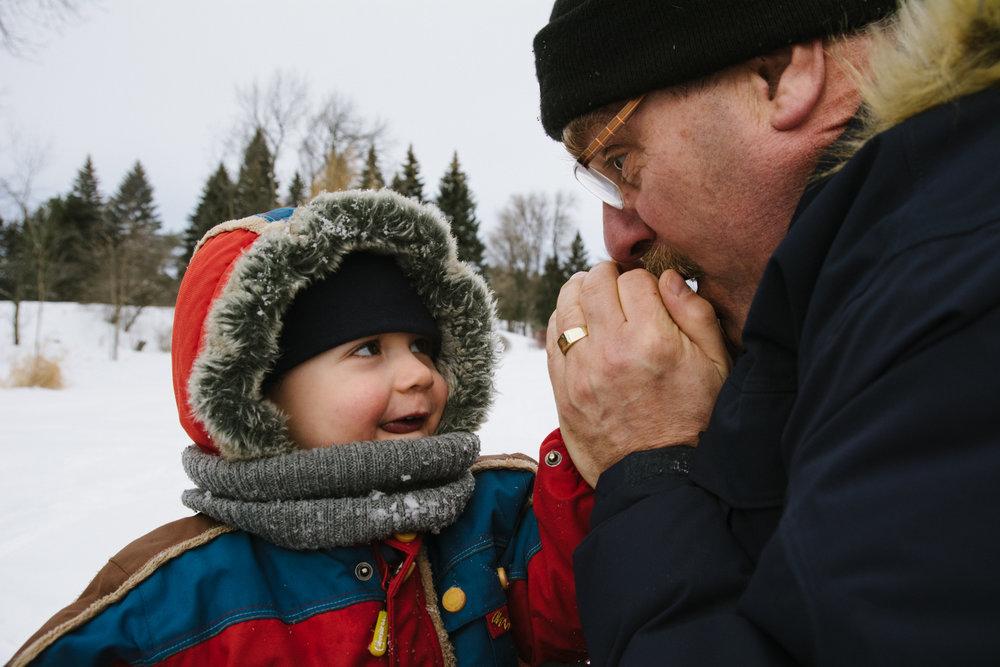 photo-d-un-grand-pere-qui-souffle-sur-les-mains-d-un-enfant-pour-les-rechauffer-photographe-enfant-famille-montreal.jpg