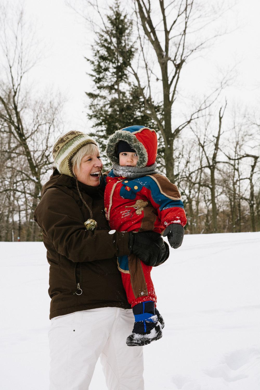 photo-d-une-grand-mere-avec-un-enfant-en-habit-de-neige-dans-les-bras-l-hiver-a-montreal-photographe-enfant-famille-montreal-2.jpg