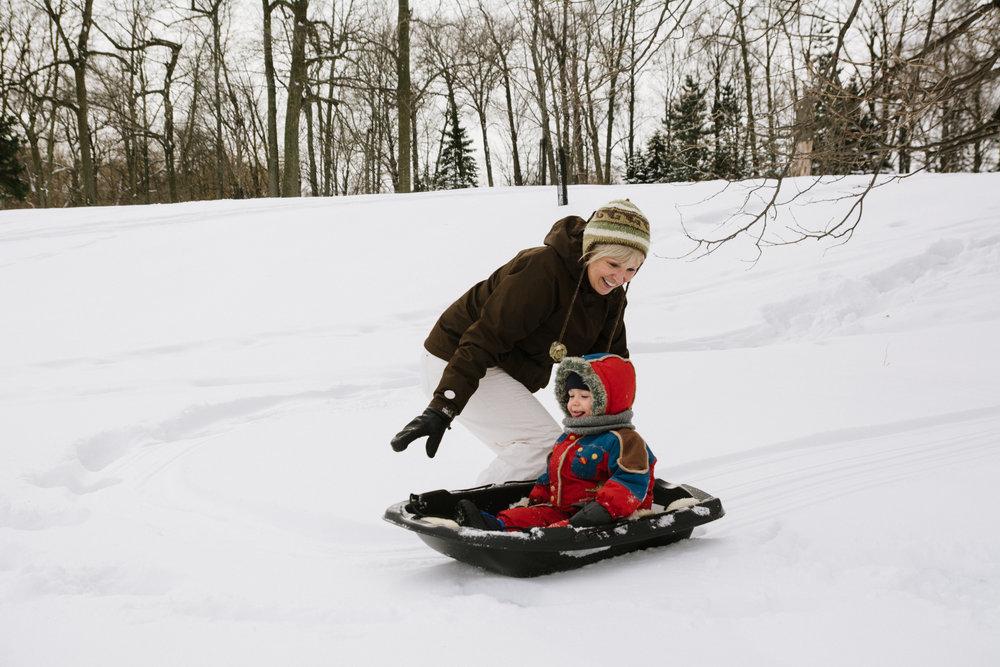 photo-d-une-grand-mere-avec-un-enfant-qui-glisse-en-traineau-l-hiver-a-montreal-photographe-enfant-famille-montreal.jpg