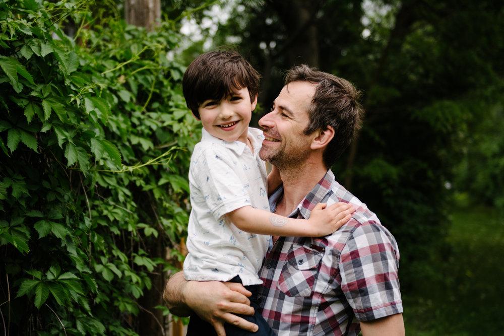 photo-d-un-pere-heureux-tenant-son-fils-dans-ses-bras-dans-une-ruelle-a-montreal-photographe-famille.jpg