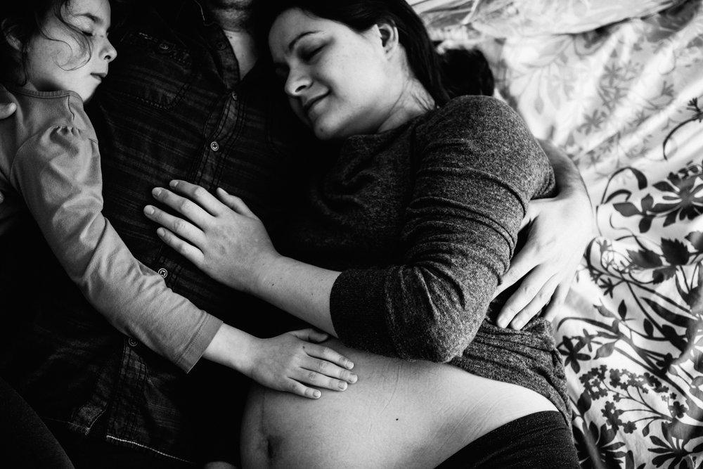 photo-noir-et-blanc-d-une-femme-enceinte-et-sa-famille-couchee-sur-un-lit-photographe-famille-maternite-montreal.jpg