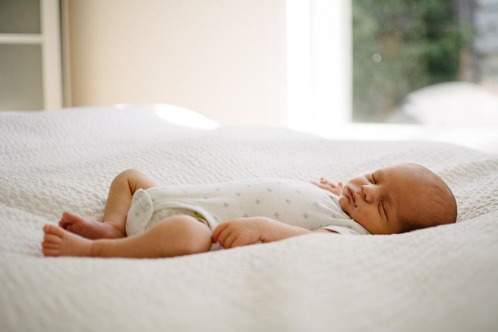 photo-des-parties-du-corps-dun-nouveau-ne-endormi-sur-un-lit_photographe-lifestyle-famille-montreal-2.jpg