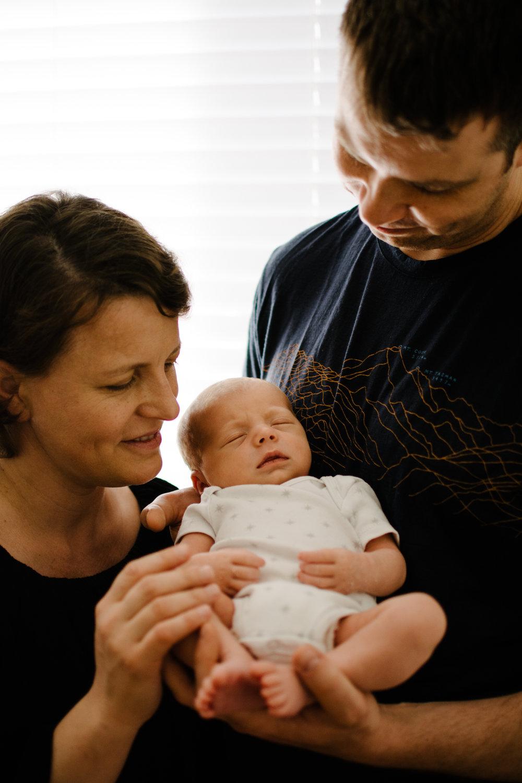 photo-de-parents-admirant-leur-nouveau-ne-dans-la-chambre-de-bebe_photographe-lifestyle-famille-montreal.jpg