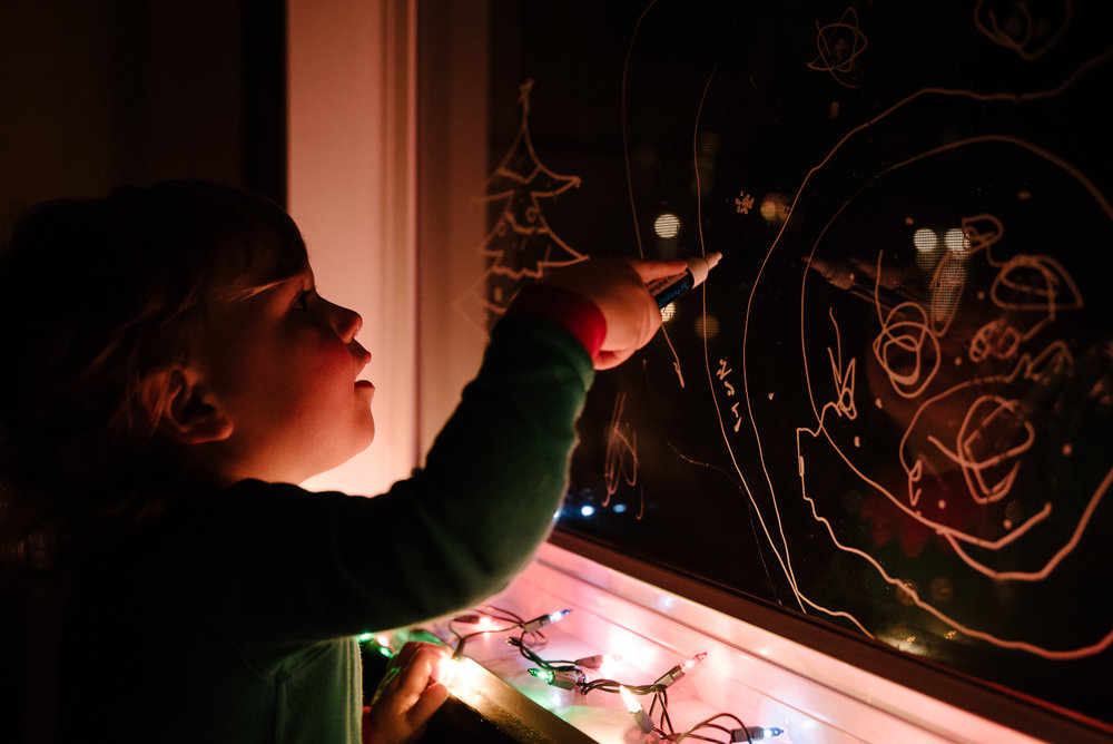 018-photo-dun-enfant-deguise-en-lutin-qui-dessine-avec-un-crayon-craie-dans-une-fenetre-photographe-lifestyle-famille-a-montreal-1456.jpg