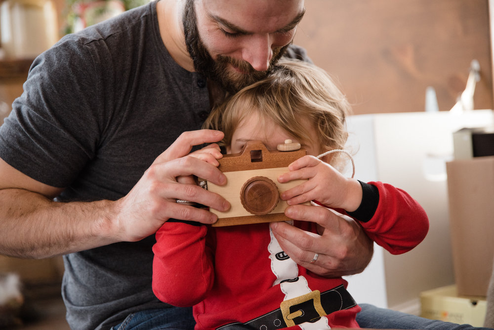 025_photo-d-un-enfant-deguise-en-pere-noel-qui-joue-avec-une-camera-jouet-en-bois-photographe-famille-enfant-a-montreal-065.jpg