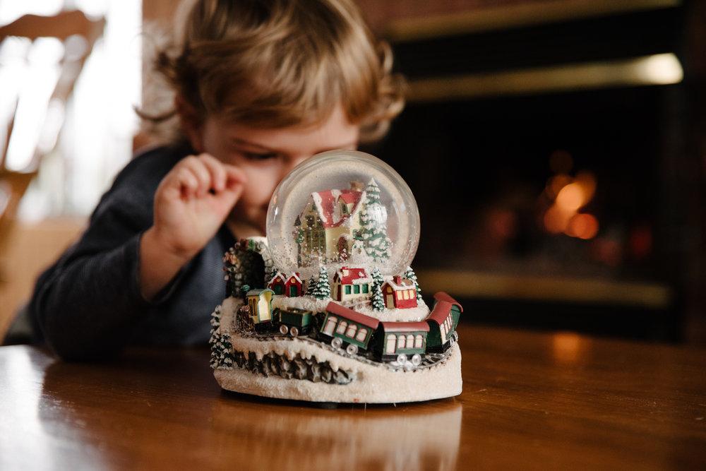 024_photo-d-un-enfant-qui-observe-une-boule-de-neige-de-noel-devant-un-feu-de-foyer-photographe-lifestyle-famille-enfant-a-montreal-035.jpg