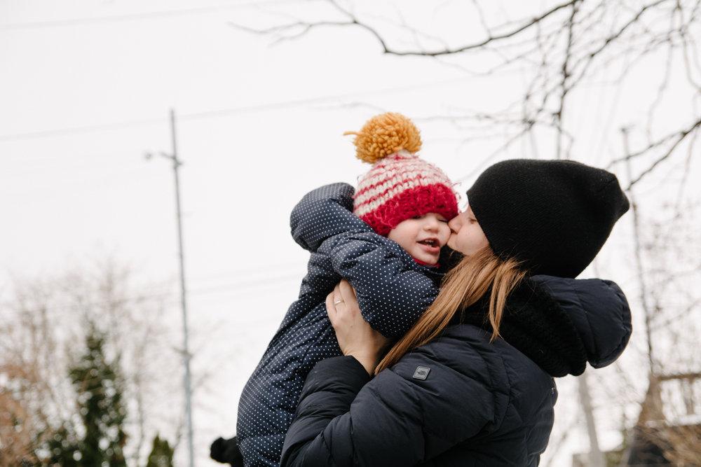 photo-dune-maman-qui-embrasse-son-bebe-emmitoufle-dans-leurs-habits-de-neige-l-hiver-photographe-famille-lifestyle-a-montreal-150.jpg
