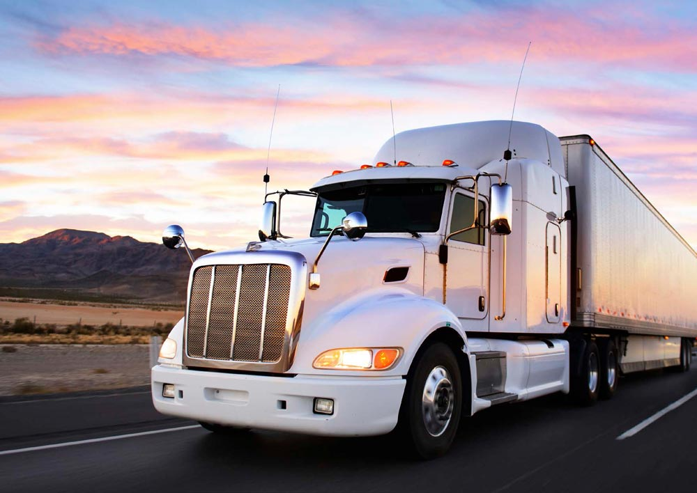 large-white-semi-frontal-view-on-highway-while-sun-is-setting.jpg
