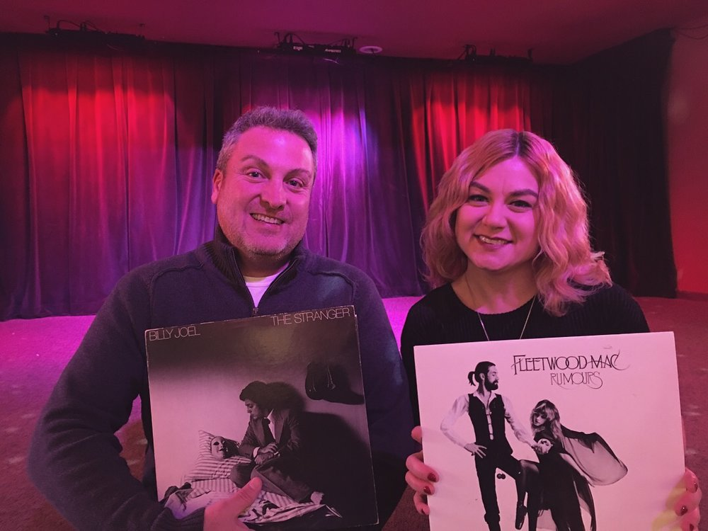 Mike and Alicia holding the albums they'll be performing on March 23